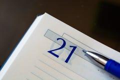 Öppna dagbokanteckningsboken med en penna Öppna på ett ark med datum 21 Royaltyfria Bilder