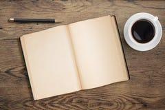 Öppna dagboken med penn- och kaffekoppen på gammalt trä Royaltyfria Foton