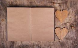 Öppna dagboken med tomma wood sidor och två valentin valentin för dag s kopiera avstånd Arkivbild