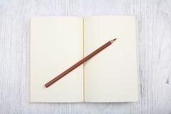 Öppna den bruna anteckningsboken och en blyertspenna på den vita trätabellen, bästa sikt Fotografering för Bildbyråer