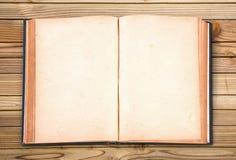Öppna den gamla tappningboken på den wood tabellen Arkivbilder