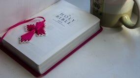 Öppna den heliga bibeln med ett kors med en kopp kaffe på en vit bakgrund royaltyfri fotografi