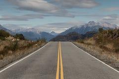 Öppna den stenlade vägen till och med berg, Patagonia, Argentina Royaltyfria Foton