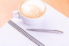 Öppna den tomma anmärkningsboken med kaffekoppen på tabellen Arkivfoton