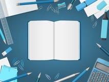 Öppna den tomma anteckningsboken med skolatillförsel Arkivfoto