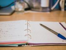 Öppna den tomma anteckningsboken på tabellen med pennan Arkivfoton