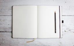 Öppna den tomma notepaden med tomma sidor med en blyertspenna Royaltyfria Bilder
