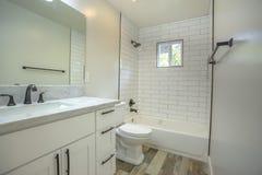 Öppna det ljusa vita badrummet med det mörka wood golvet, och duschen badar i för den sydliga Kalifornien för modellhemmet forsen fotografering för bildbyråer