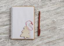 Öppna en tom anteckningsbok och en träjulgarnering - julgran Royaltyfria Foton