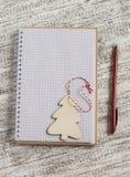 Öppna en tom anteckningsbok och en träjulgarnering - julgran Arkivfoto