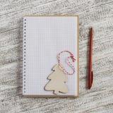 Öppna en tom anteckningsbok och en träjulgarnering - julgran Royaltyfri Foto