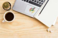 Öppna en tom vit anteckningsbok med blyertspennan, bärbara datorn och en kopp av cof Arkivfoto