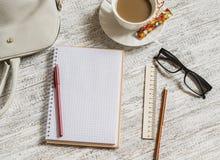 Öppna en tom vit anteckningsbok, penna, kvinnors påse, linjal, blyertspenna och kopp kaffe Royaltyfri Bild