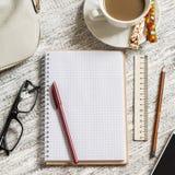 Öppna en tom vit anteckningsbok, penna, kvinnors påse, linjal, blyertspenna och kopp kaffe Arkivfoto