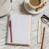 Öppna en tom vit anteckningsbok, penna, kvinnors påse, linjal, blyertspenna och kopp kaffe Fotografering för Bildbyråer