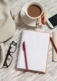 Öppna en tom vit anteckningsbok, penna, kvinnors påse, telefon, linjal, blyertspenna och kopp kaffe arkivfoto