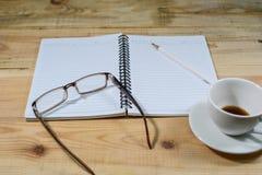 Öppna en tomma vita anteckningsbok, blyertspenna, kaffe och exponeringsglas på träskrivbordet Arkivfoton