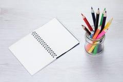 Öppna färgade blyertspennafärgpennor för anteckningsbok tillsammans med Royaltyfri Bild