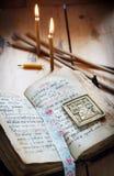 Öppna forntida bok- och bränningstearinljus Arkivfoton