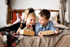 Öppna gåvor för flicka och för pojke glada lyckliga ferier för jul Royaltyfria Foton