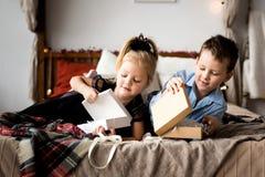 Öppna gåvor för flicka och för pojke glada lyckliga ferier för jul Royaltyfri Foto