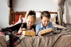 Öppna gåvor för flicka och för pojke glada lyckliga ferier för jul Arkivbild
