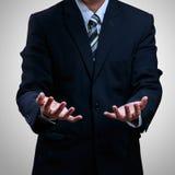 Öppna händer för affärsman som visar något Arkivfoto
