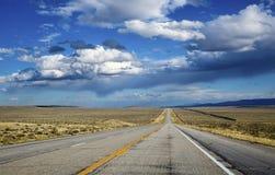 Öppna huvudvägen som ut sträcker in i avståndet under molniga blått Arkivfoton