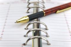 Öppna kalendern med pennan arkivbild