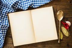 Öppna kokboken med kitchenware Fotografering för Bildbyråer