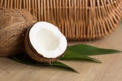 Öppna kokosnöten på rottingbakgrund Arkivbilder