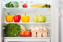 Öppna kylskåpet mycket av frukter och grönsaker Arkivfoto