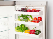 Öppna kylskåpet mycket av nya frukt och grönsaker Arkivbild