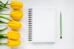 Öppna notepad, blyertspenna och gulingtulpan Royaltyfri Fotografi