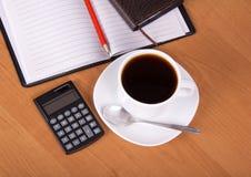 Öppna notepaden, räknemaskinen, kopp kaffe Arkivfoto