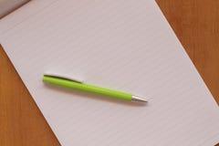 Öppna och tomma sidor av en anteckningsbok och en penna Royaltyfria Foton