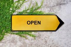 Öppna på det gula tecknet som hänger på murgrönaväggen Arkivbild