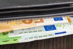Öppna plånboken med eurokassa 10 20 50 100 på en träbakgrund Plånbok för man` s med kontant euro Royaltyfri Fotografi