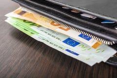 Öppna plånboken med eurokassa 10 20 50 100 på en träbakgrund Plånbok för man` s med kontant euro Fotografering för Bildbyråer