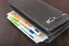 Öppna plånboken med eurokassa 10 20 50 100 på en träbakgrund Plånbok för man` s med kontant euro Royaltyfri Foto