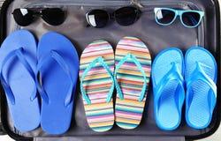 Öppna resväskan med badskor och solglasögon, closeup royaltyfri foto