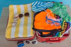 Öppna resväskan med olik saker Lopp- och semesterbegrepp Öppna traveler& x27; s-påse med kläder, tillbehör Royaltyfri Foto