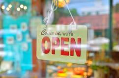 Öppna tecknet som är brett till och med exponeringsglaset av fönstret Royaltyfria Foton