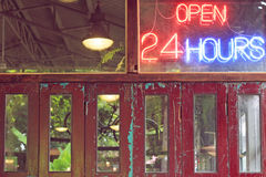 Öppna 24 timmar neontecken på väggen Fotografering för Bildbyråer