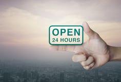 Öppna 24 timmar symbol på fingret över stadstorn Fotografering för Bildbyråer
