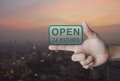 Öppna 24 timmar symbol på fingret Arkivbilder