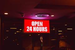 Öppna 24 timmar, tecken sombanret shoppar in Royaltyfri Foto