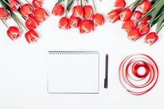 Öppna tomma anteckningsbok, penna och buketter av röda tulpan Royaltyfria Foton