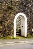Öppna trädörren med den spetsiga gotiska bågen på en vit stenvägg royaltyfri fotografi