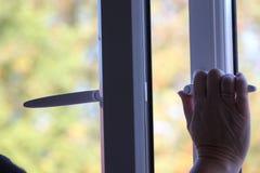 Öppna upp och stäng ett vitt fönster Damhand royaltyfri foto